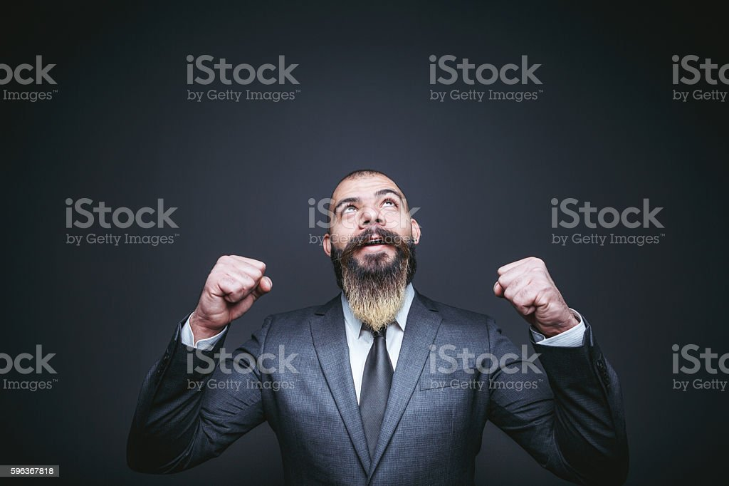 Businessman cheering with arms outstretched stock photo