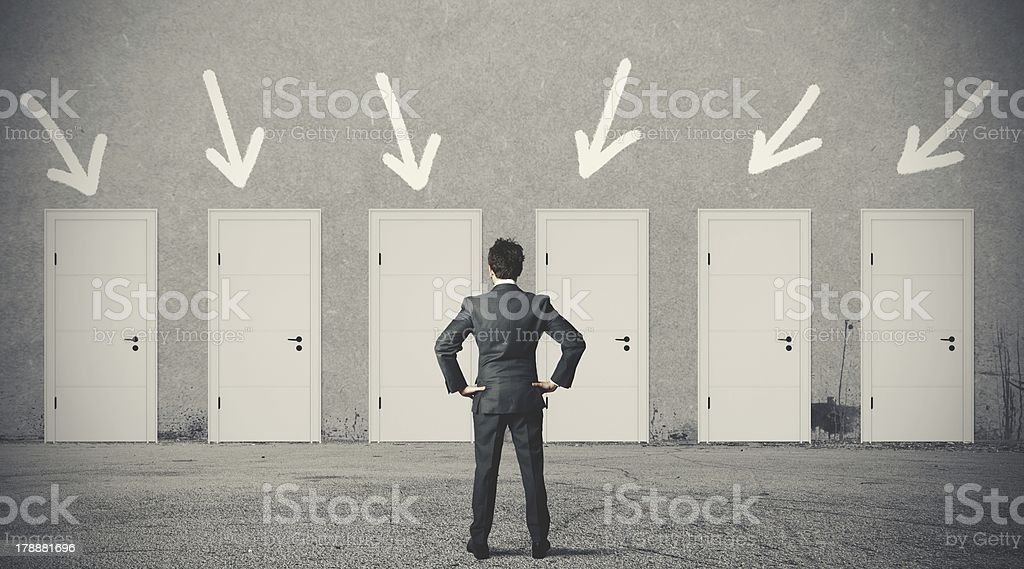 Businessman choosing the right door stock photo