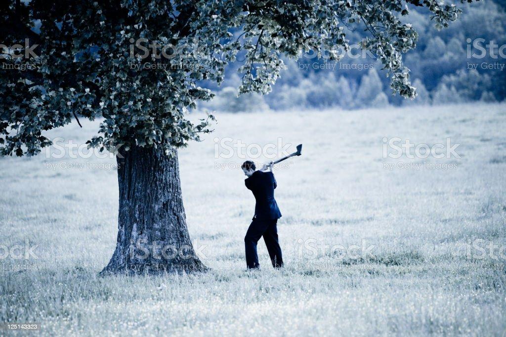 Businessman chopping down a tree stock photo