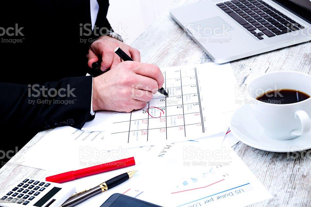 Businessman circling important dates on his calendar stock photo