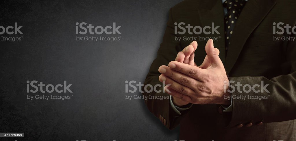 Businessman clapping - blackboad in background stock photo