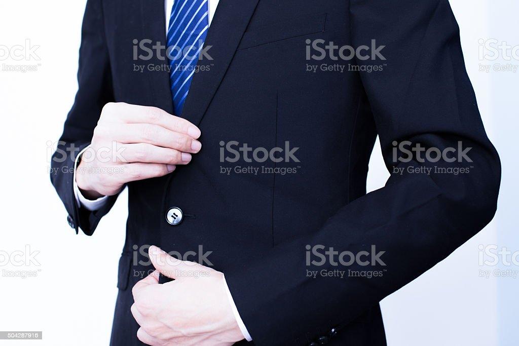 businessman clasps a jacket button stock photo