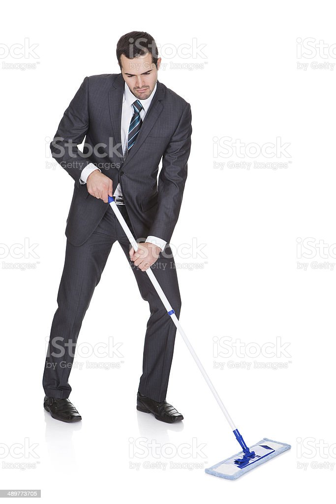 Businessman cleaning floor stock photo