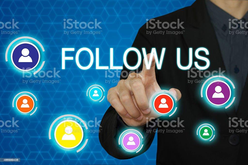 Businessman click Follow us people. stock photo