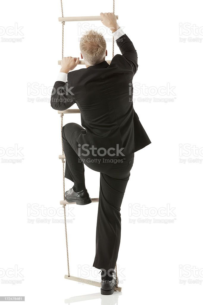 Businessman climbig a rope ladder stock photo