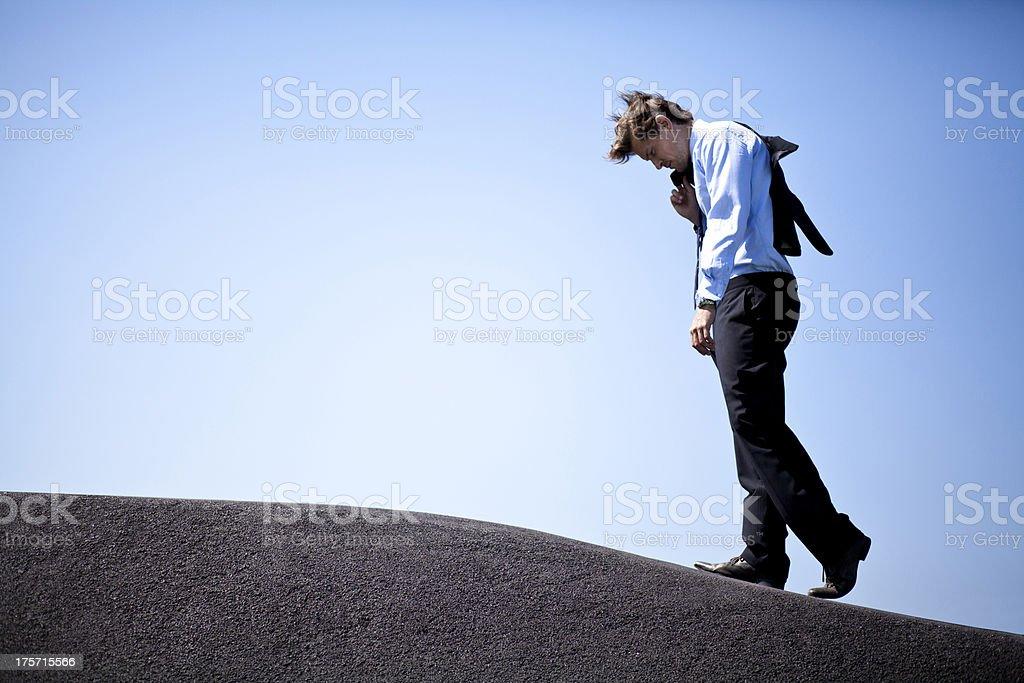 Businessman climbing a hill stock photo