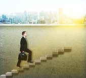 businessman climbing concrete ladder