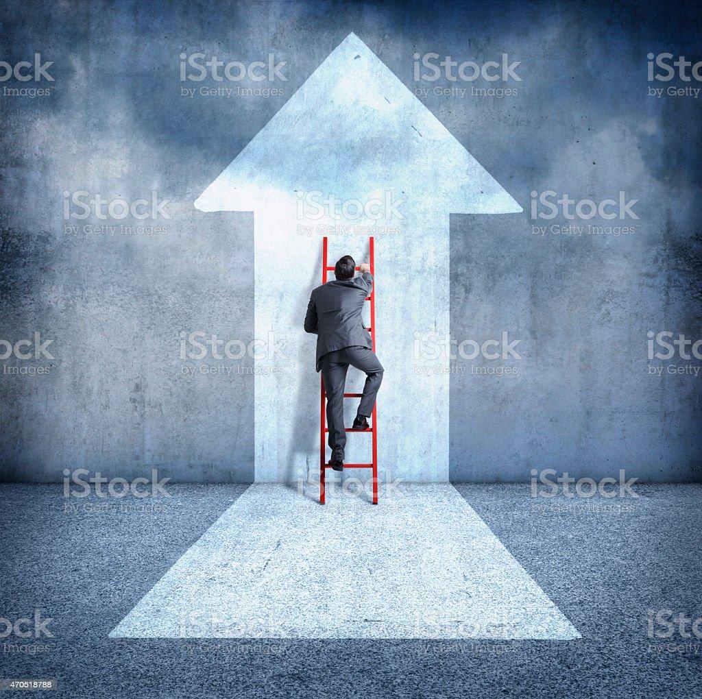 Businessman climbing ladder towards success stock photo