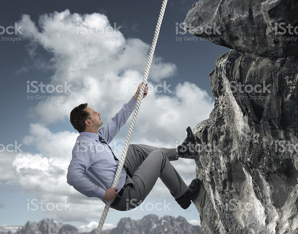 Businessman climbing mountain stock photo