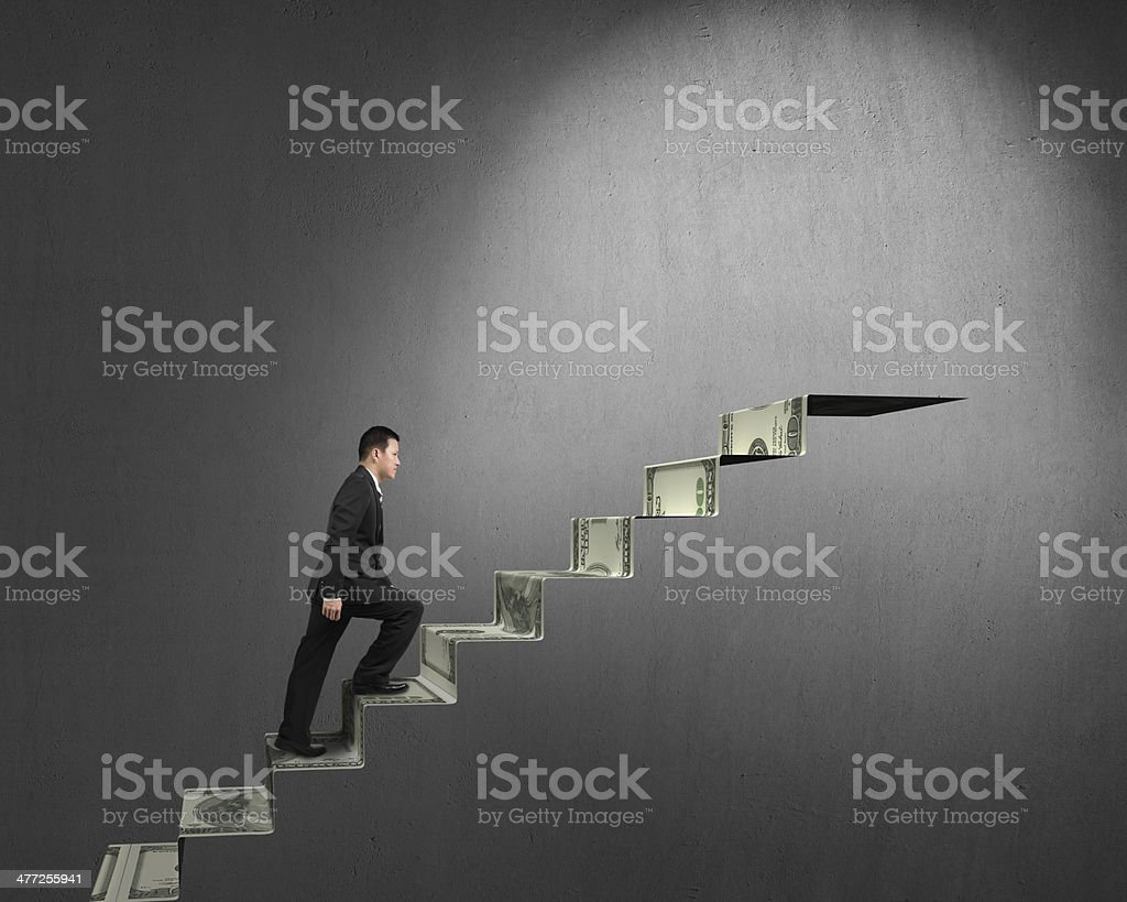 Businessman climbing on money stairs to top stock photo