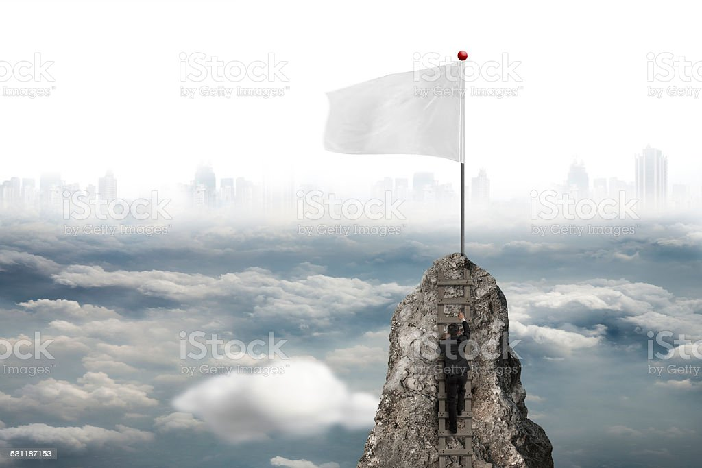 Businessman climbing on peak with white flag and cloudy cityscap stock photo