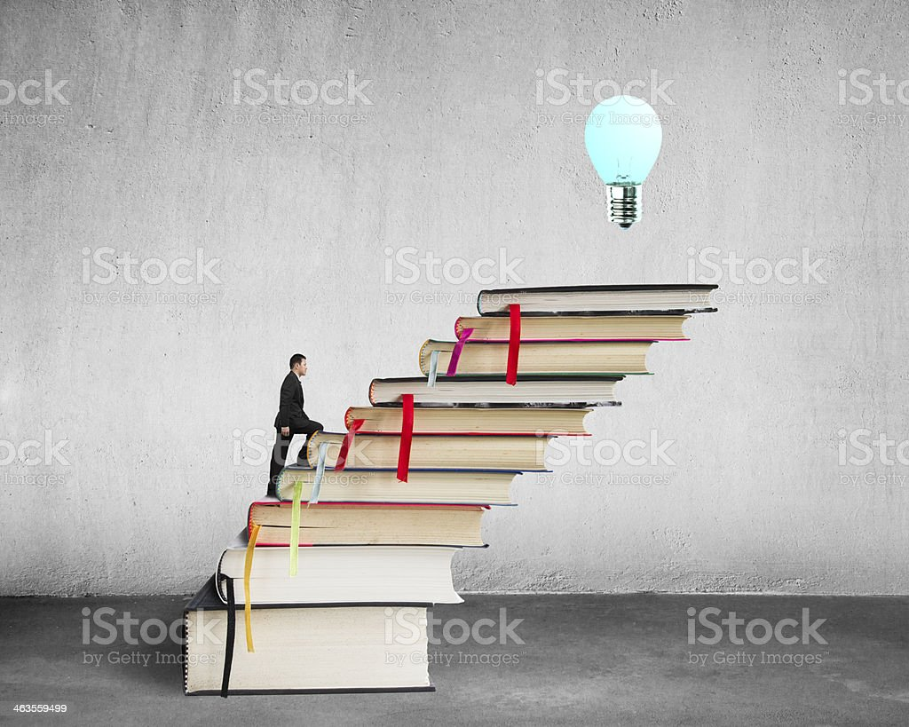 Businessman climbing on stack of books with growing bulb stock photo