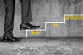 Businessman climbing on steps to achieve success