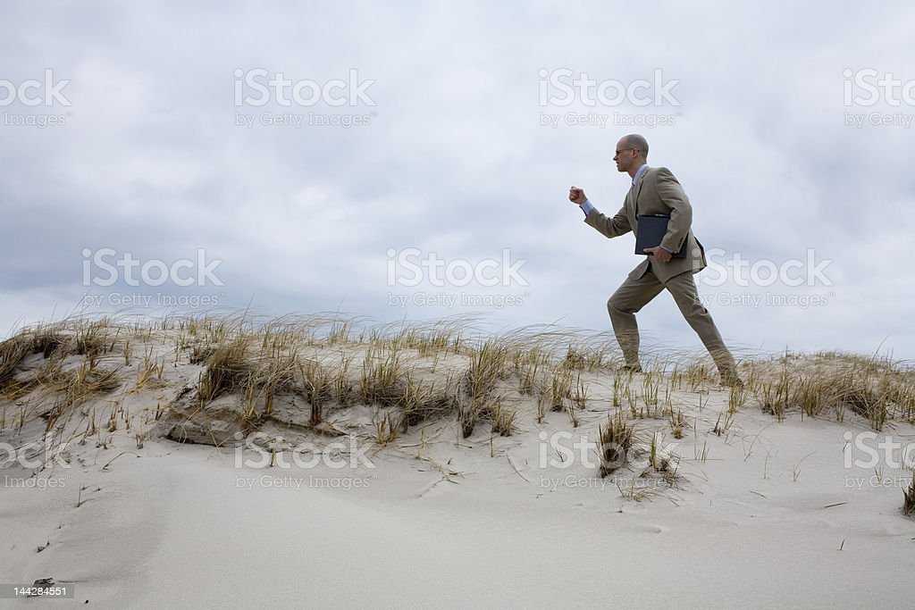 Businessman Climbing on the Sand Dune stock photo
