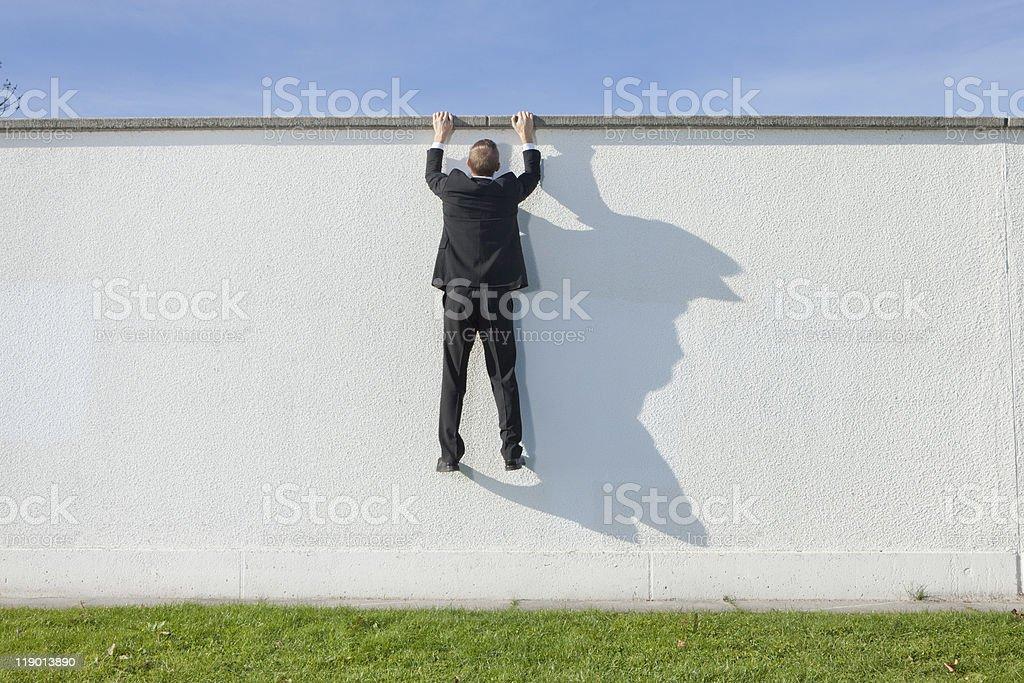 Businessman climbing over wall stock photo