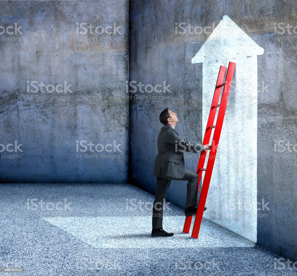 Businessman Climbing Red Ladder Leaning Against Wall With Arrow stock photo