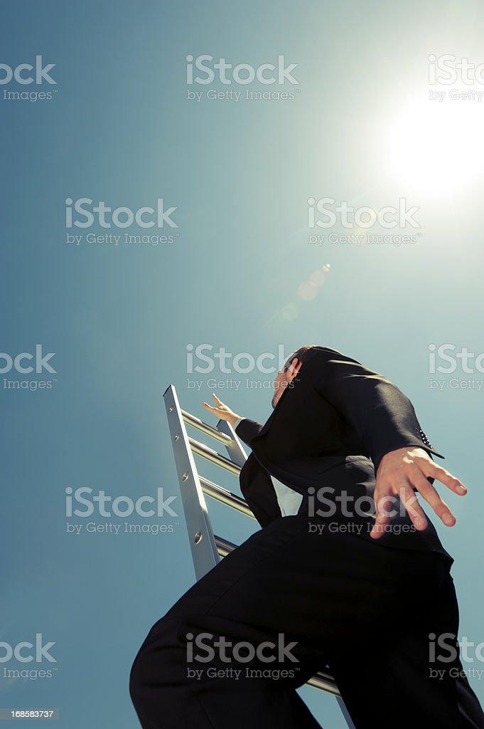 Businessman climbing the Ladder of success stock photo