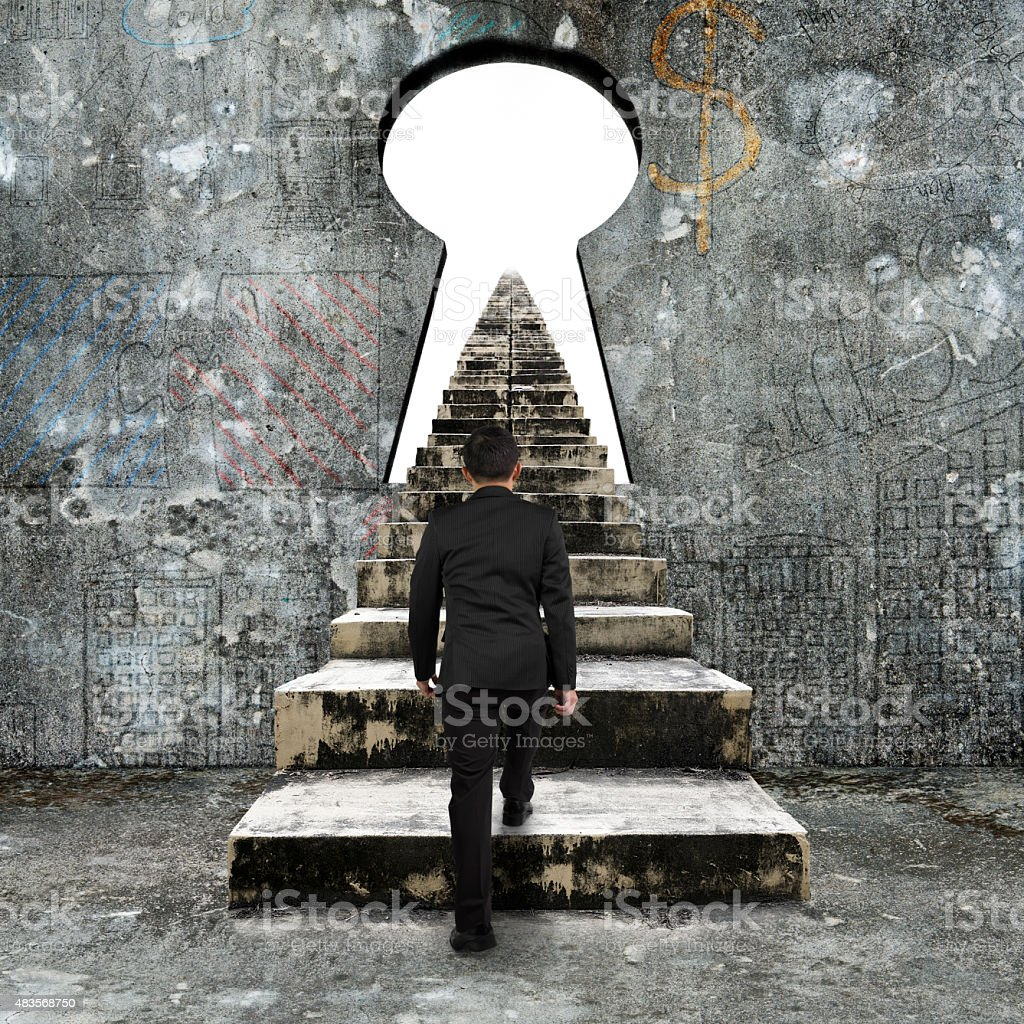 Businessman climbing the old concrete stairs toward keyhole stock photo