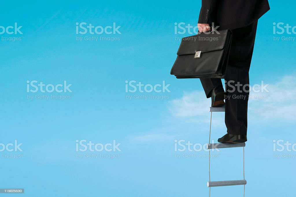 Businessman climbs ladder royalty-free stock photo