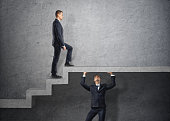 Businessman climbs the concrete stairs, which the other person keeps.