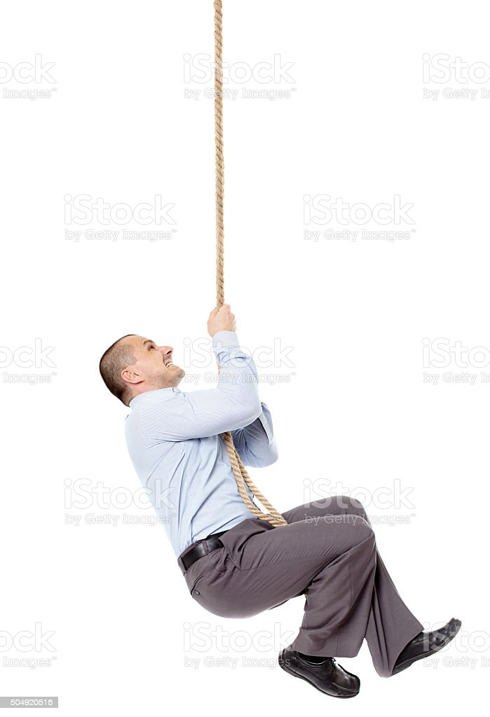Businessman climing on a rope stock photo