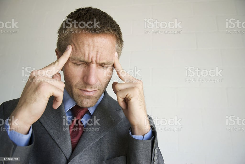 Businessman Closes Eyes and Holds Fingers to Temples stock photo