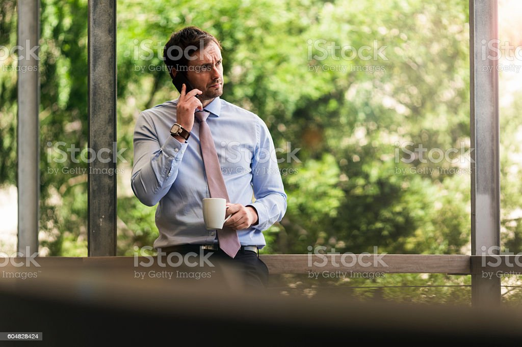 Businessman coffee cup using mobile phone stock photo