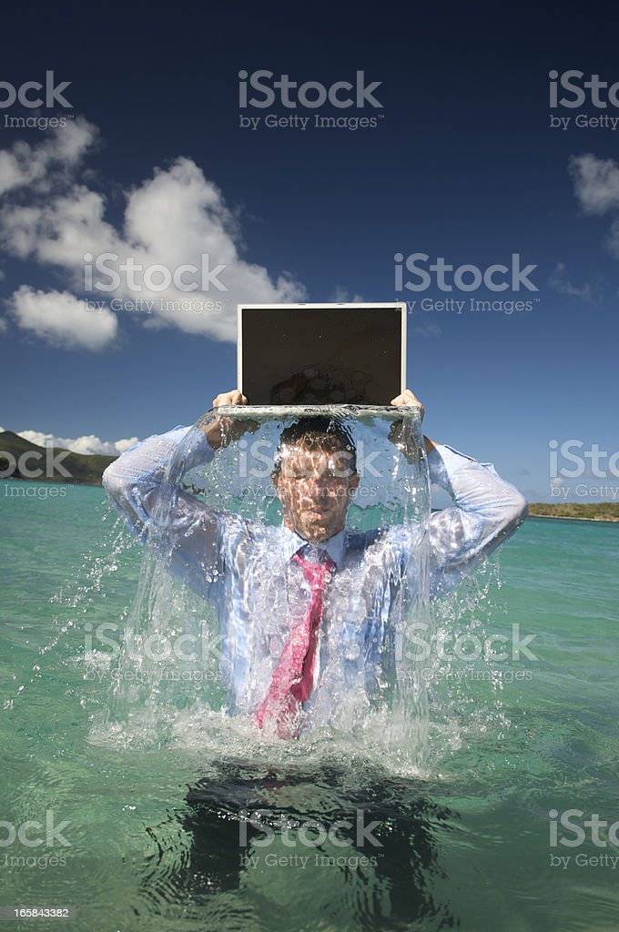 Businessman Comes Splashing Out of Water with Laptop stock photo