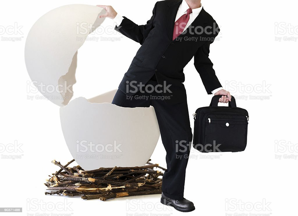 Businessman coming out of a giant egg shell in a large nest stock photo