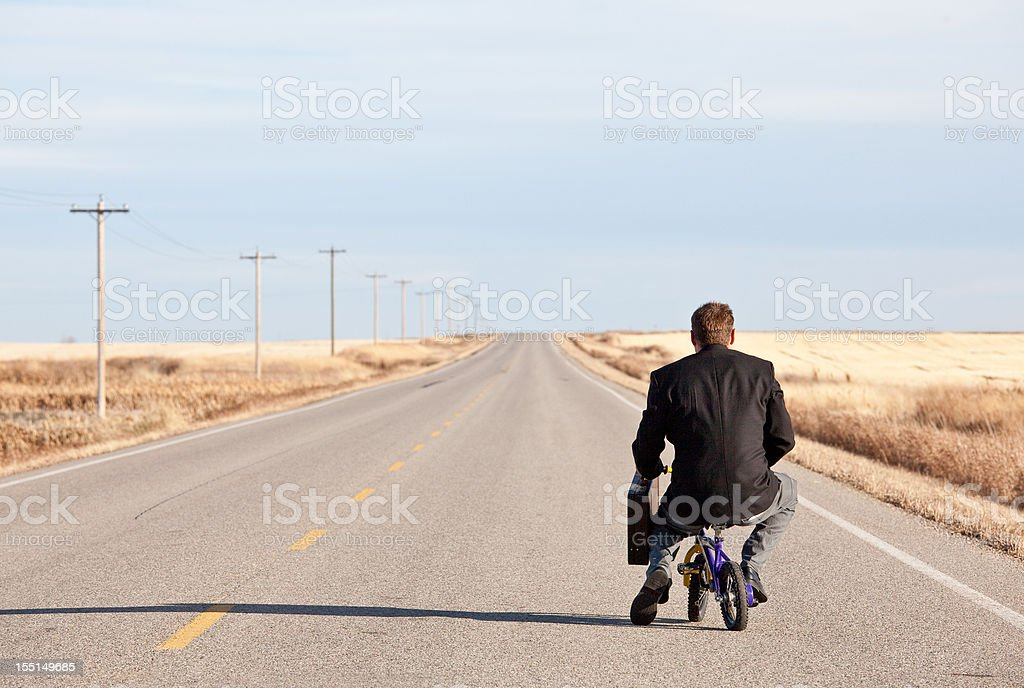 Businessman Commuting on Tiny Bicycle stock photo