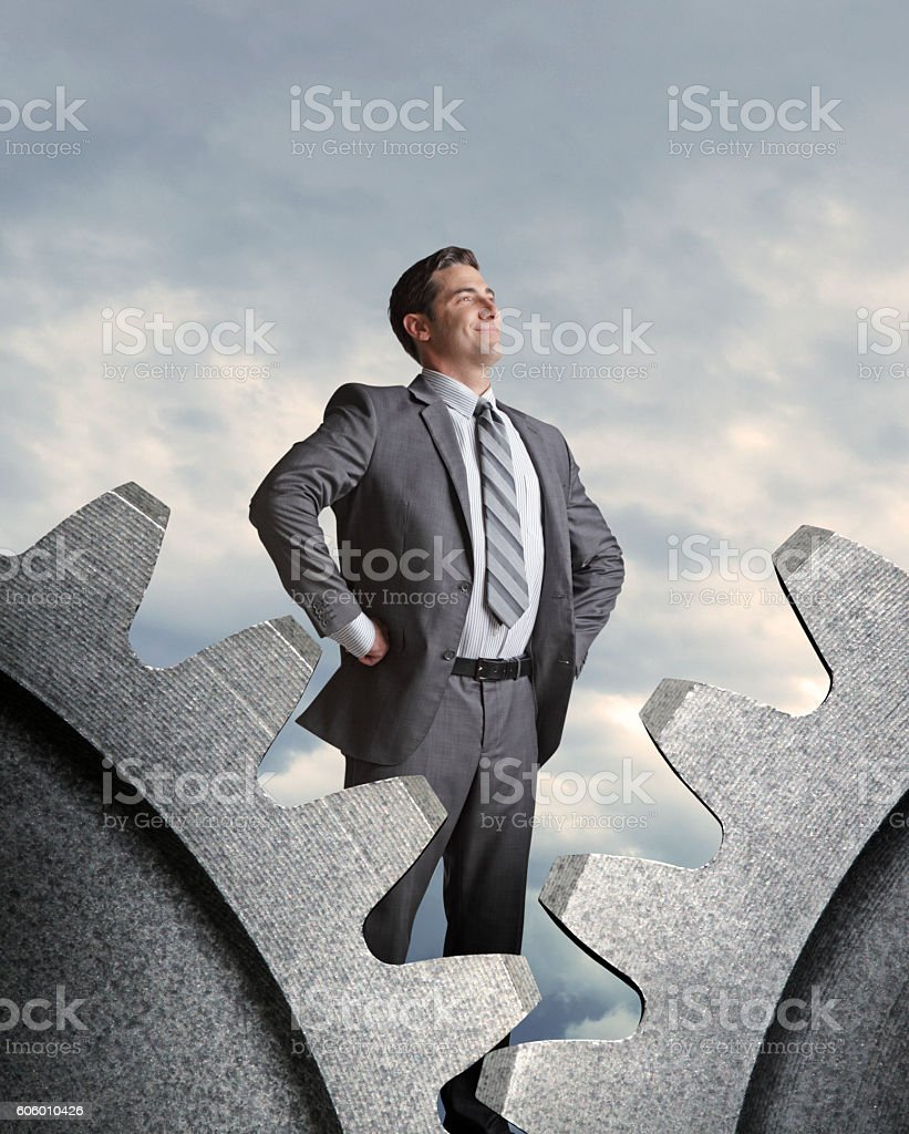 Businessman Confidently Stands Behind Two Interlocking Gears stock photo