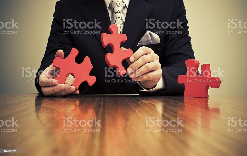 Businessman connect two large jigsaw pieces royalty-free stock photo