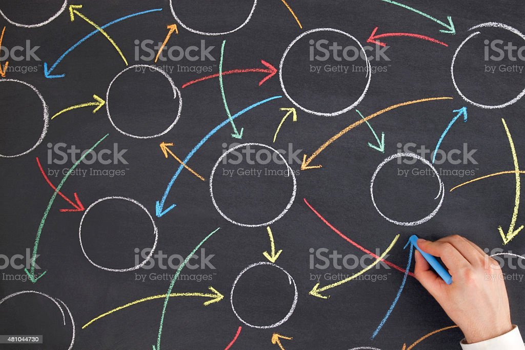 Businessman Connecting Circles with Colorful Arrows on Blackboard stock photo