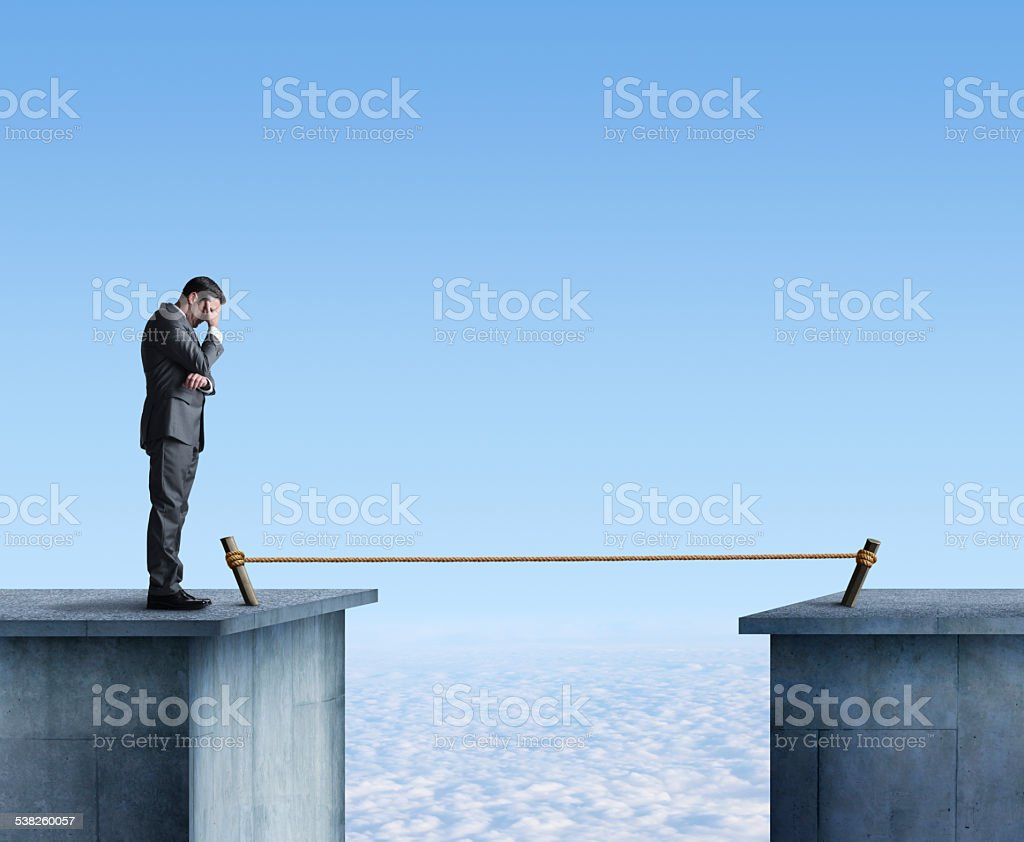 Businessman Contemplating Having To Cross A Tightrope stock photo