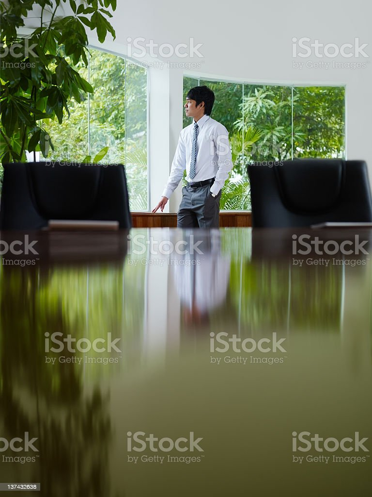 businessman contemplating out of window in meeting room royalty-free stock photo