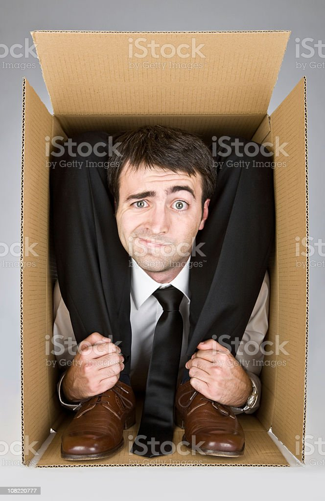 Businessman contorted in a box over a white background stock photo