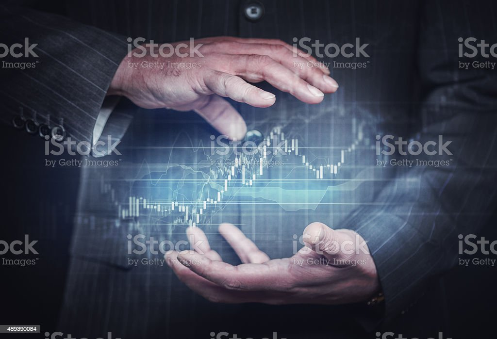 Businessman controlling financial charts stock photo