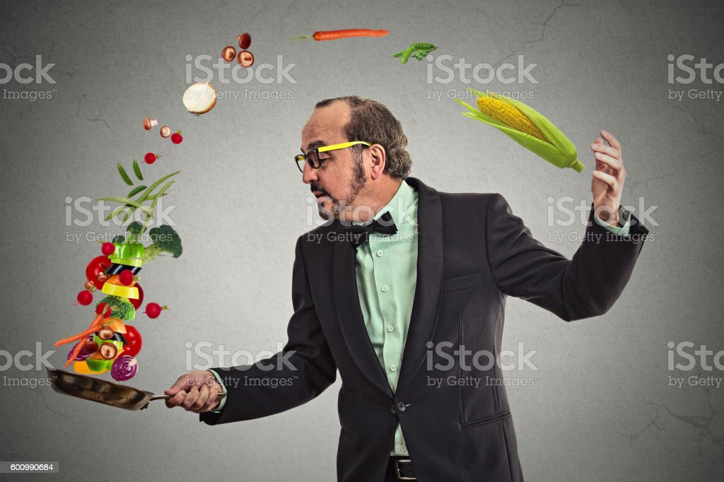 Businessman cooking vegetables with a pan stock photo