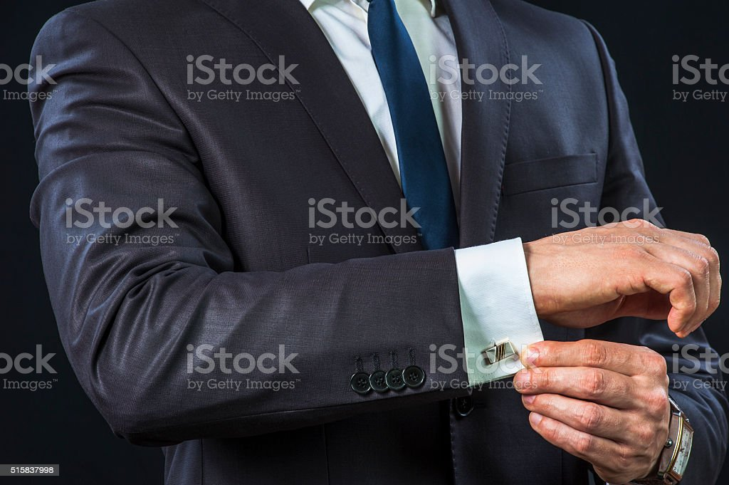 Businessman correcting cufflinks stock photo