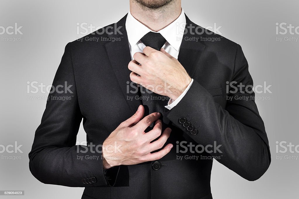 businessman correcting his tie stock photo