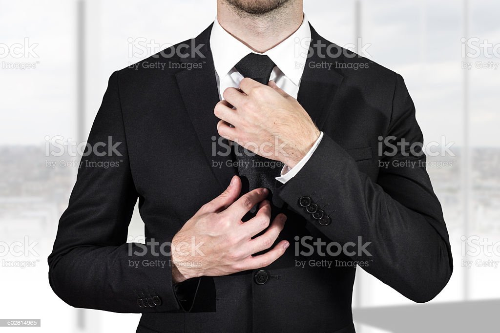 businessman correcting necktie stock photo
