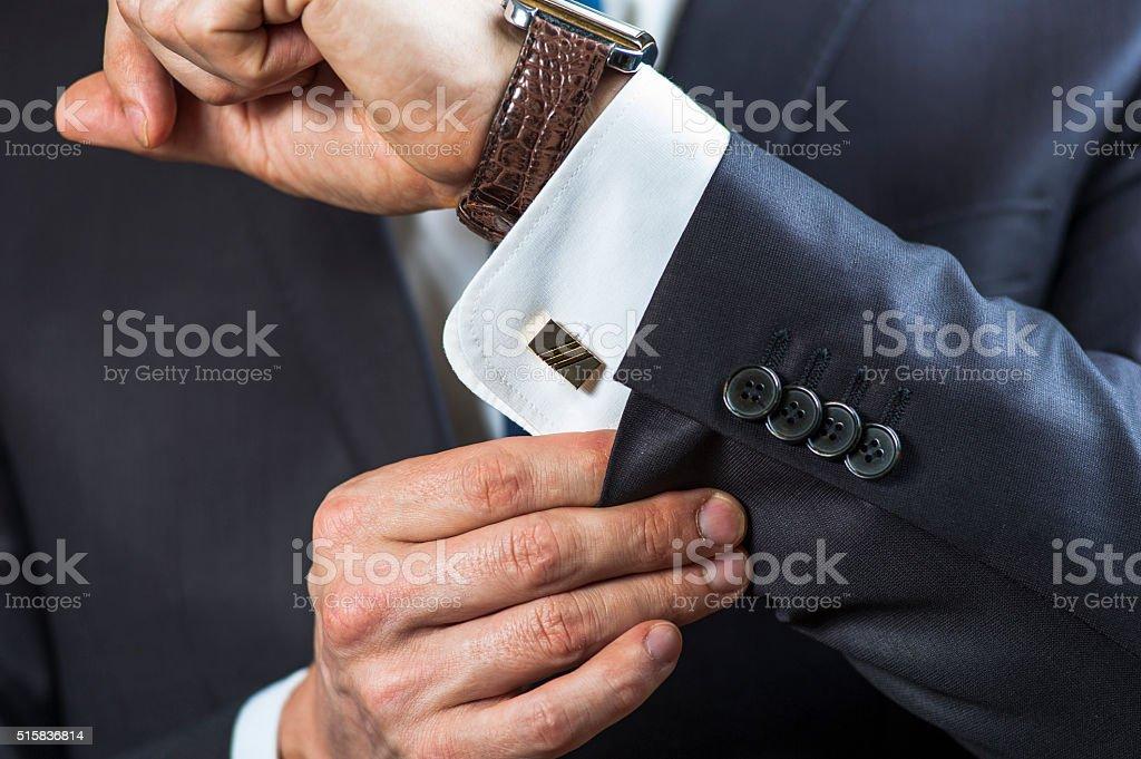 Businessman correcting shirt sleeve stock photo