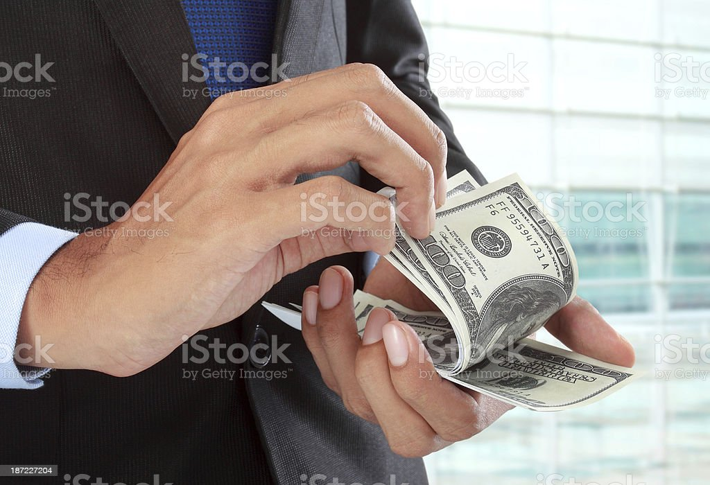 A businessman counting a stack of hundred dollar bills royalty-free stock photo