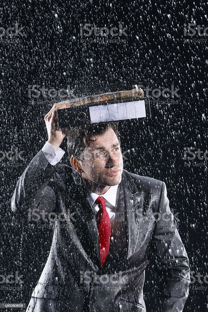 Businessman Covering Head With Binder In Rain stock photo