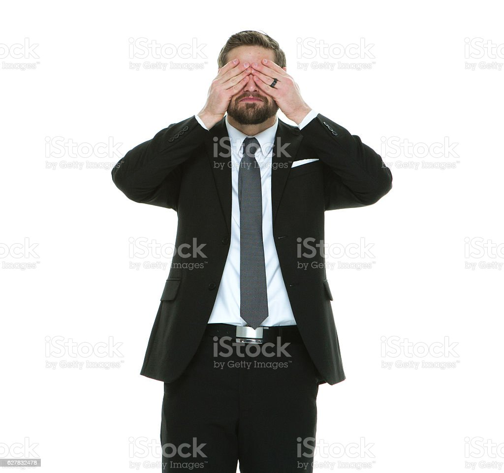 Businessman covering his eyes stock photo