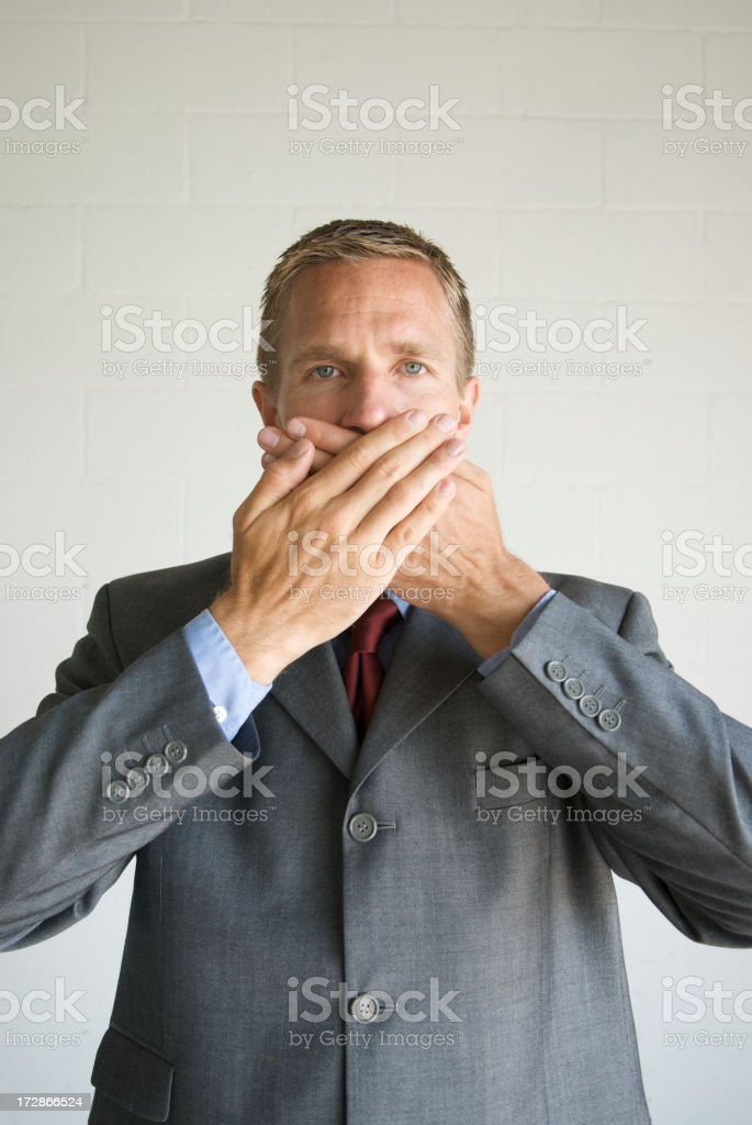 Businessman Covers Mouth to Speak No Evil stock photo