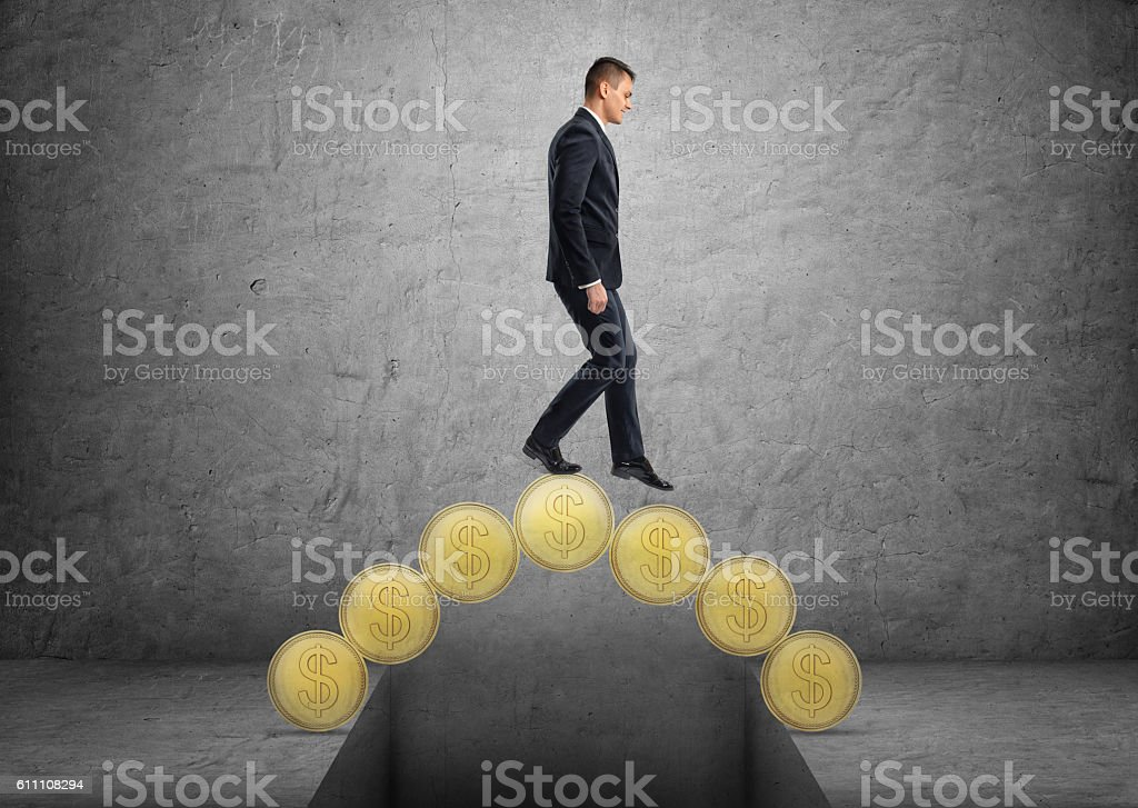 Businessman crossing a bridge made of golden coins stock photo