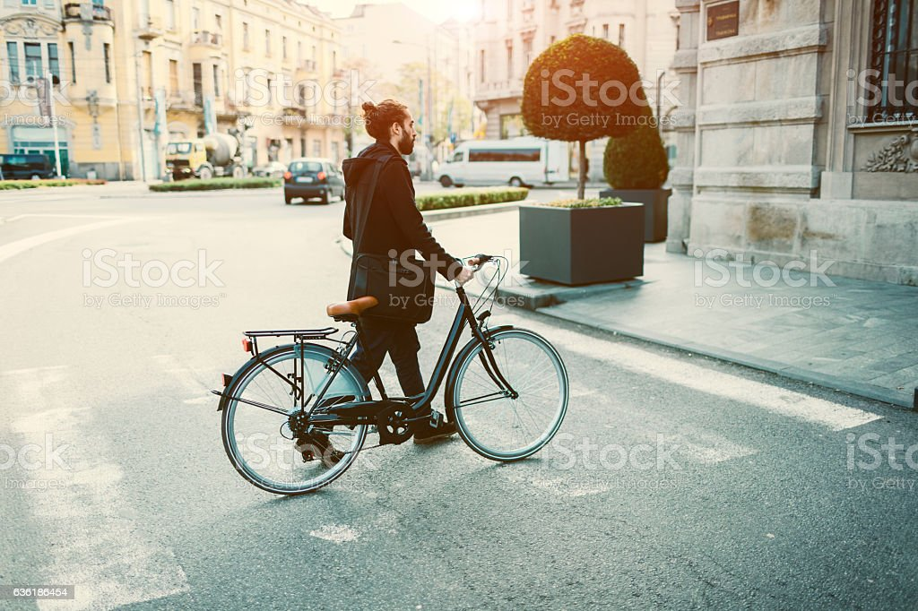Businessman Crossing The Street With Bicycle. stock photo