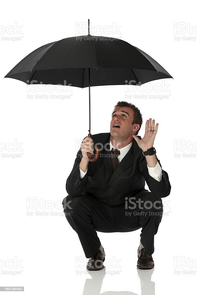 Businessman crouching under umbrella royalty-free stock photo