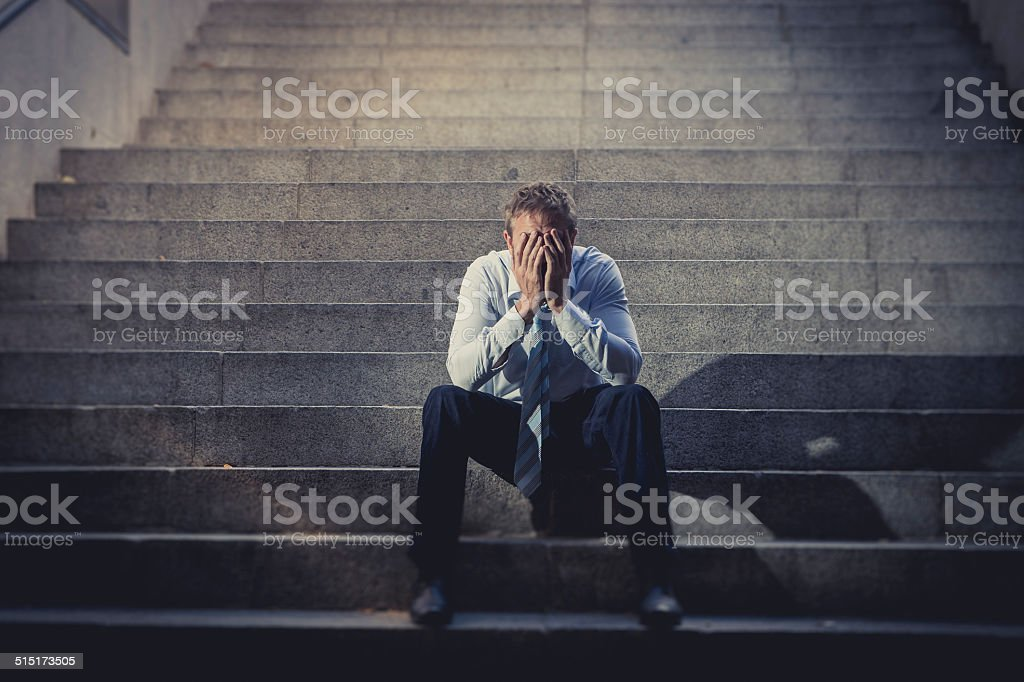 businessman crying lost in depression sitting on street concrete stairs stock photo